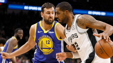 LaMarcus Aldridge dribbles the ball beside returning NBA player Andrew Bogut.