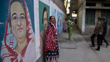 A women stands next to a mural displaying a portrait of Bangladesh's Prime Minister Sheikh Hasina at a polling station in Dhaka on Sunday.
