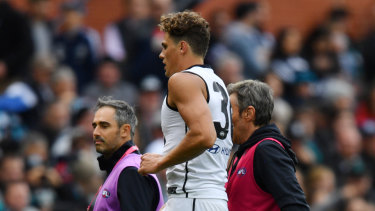 Charlie Curnow is helped from the field.