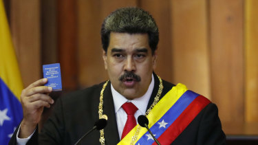 Nicolas Maduro with a tiny copy of the constitution during his swearing in as president on January 10.