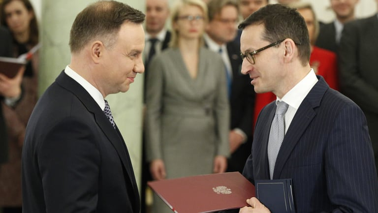 Polish President Andrzej Duda, left, hands Prime Minister Mateusz Morawiecki the document of his appointment last December.