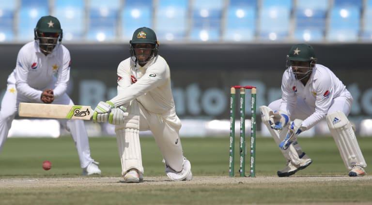 Defiant: Australian opener Usman Khawaja reverse-sweeps on his way to his seventh Test century.
