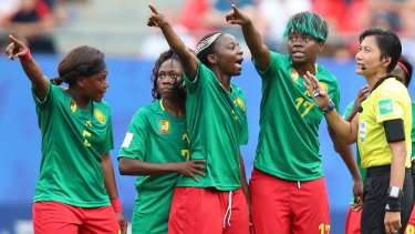 Flashpoint: Cameroon's players argue with referee Qin Liang of China in Valenciennes.