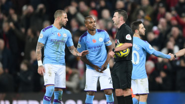 Manchester City players speak to match referee Michael Oliver.