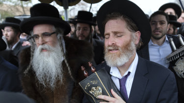 Orthodox Jews in Monsey, New York,  celebrate the arrival of a new Torah a day after an attack on their community.