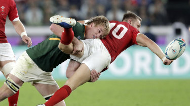 Wales' Dan Biggar, right, passes while being tackled by South Africa's Pieter-Steph du Toit.