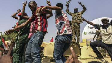 Sudanese men celebrate in April after officials said the military had forced longtime autocratic President Omar al-Bashir to step down.