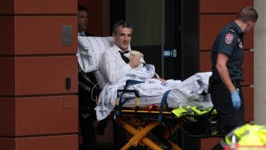 Terry McMaster leaves the Federal Court with the aid of paramedics after collapsing while being questioned.