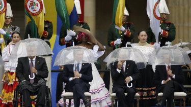 From left, Ecuador's President Lenin Moreno, Argentina's Mauricio Macri, Chile's Sebastian Pinera and Mexico'sEnrique Pena Nieto hold umbrellas during the presidential inauguration of Ivan Duque, in Bogota, Colombia.