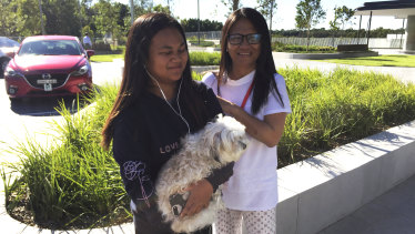 Lanie Devera, with her daughter Avril, 12, and dog Coco, outside Opal Tower in Olympic Park.