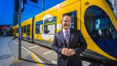 Gold Coast Mayor Tom Tate standing in front of the light rail network at Southport.