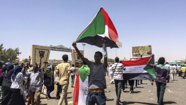 Protester display Sudanese flags at a rally in front of the military headquarters in the capital Khartoum, Sudan.