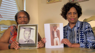 Mylinda Byrd Washington, 66, right, and Louvon Byrd Harris, 61, hold up photographs of their brother James Byrd jnr.