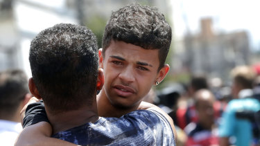 A former student is comforted by a friend outside the Raul Brasil State School in Suzano, Brazil.