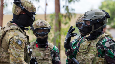 An Australian Army soldier, left, answers questions from members of the Indonesian army during joint training.
