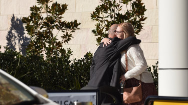 Mr Brosnan's father, Cornelius (left), embraces his son's girlfriend, Hayley Sheers, outside the NSW Coroners Court.
