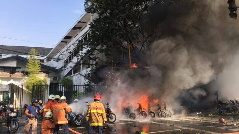 Firefighters try to extinguish a blaze following a blast at the Pentecost Church Central Surabaya (GPPS) in Surabaya.