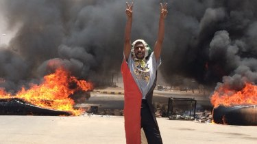 A protester stands in front of burning debris near Khartoum's army headquarters, in Khartoum, on Monday.