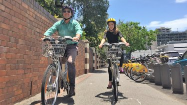 Brisbane Council deputy mayor Adrian Schrinner and Bicycle Queensland chief executive Anne Savage ride around Mater Hospital in Annerley, where a new CityCycle station has been installed.