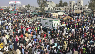 Sudanese demonstrators march with national flags as they gather during a rally demanding a civilian body to lead the transition to democracy, outside the army headquarters in the Sudanese capital Khartoum on Saturday.
