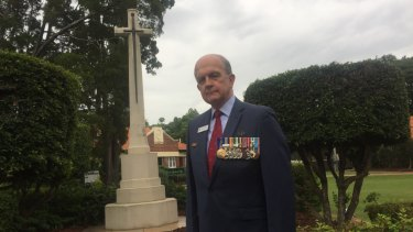 Toowong RSL branch president Kerry Gallagher AM  at the restored Cross of Sacrifice at Toowong Cemetery.
