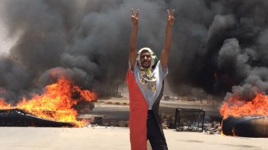 A protester flashes the victory sign in front of burning tires and debris on road 60, near Khartoum's army headquarters, in Khartoum, Sudan, before the military forces attacked,