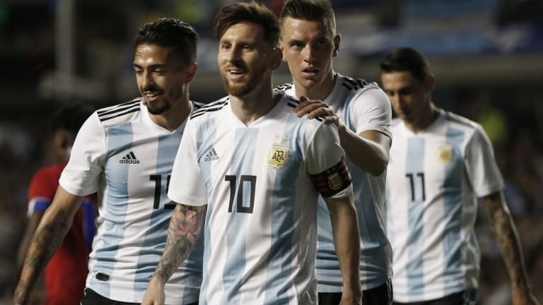 Leading from the front: Messi is congratulated by teammates after a goal.