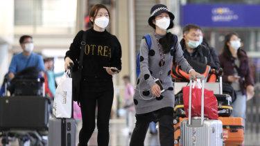 Travellers wearing face masks walk through the check-in hall at Hong Kong International Airport.