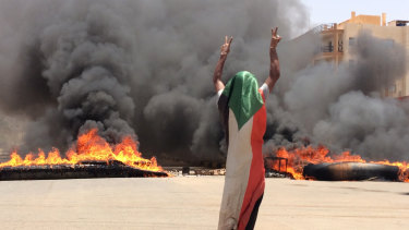 A protester wearing a Sudanese flag flashes the victory sign in front of burning tires and debris on road 60, near Khartoum's army headquarters, during the violence on Monday.
