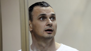 Oleg Sentsov stands behind bars as his verdict is read at a court in Rostov-on-Don, Russia, in 2015.