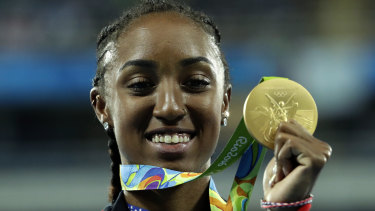 Gold medal winner Brianna Rollins from the United States shows off her medal during the medal ceremony for the women's 100-meter hurdles final during the athletics competitions of the 2016 Summer Olympics.