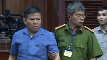 Australian man Chau Van Kham, left, is escorted into a Vietnamese court.