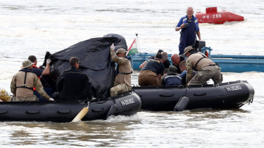 Rescuers in inflatable boats transport what appear to be bodies of victims near the Margaret Bridge where a sightseeing boat capsized in the Danube river in Budapest, Hungary.