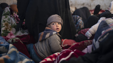 Women and children sit in the back of a truck as they wait to be screened by US-backed Syrian Democratic Forces  after being evacuated out of the last territory held by Islamic State militants last month.
