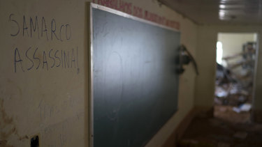 """A scrawled message in Portuguese that reads """"Samarco Assassin"""" rests on a classroom wall a year after the school was destroyed by a tsunami of mud triggered by the tailings dam failure."""
