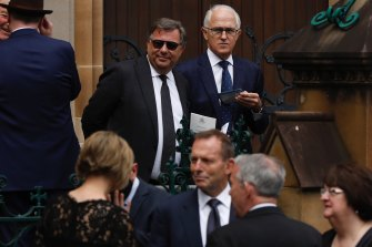 Former prime ministers Tony Abbott (below, centre) and Malcolm Turnbull  (above, right) after the funeral.