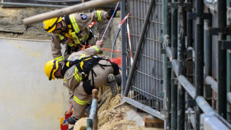 Firefighters in the pit where one man was killed and two were injured.