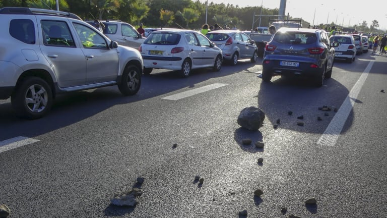 "Stones left on the highway leading to the airport in Sainte Marie on Reunion Island as protesters, called the ""yellow jackets"", block the traffic."