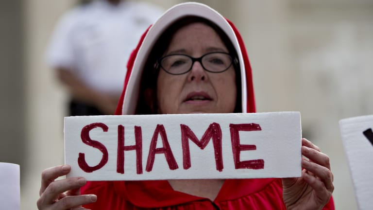 """A demonstrator dressed in """"Handmaid's Tale"""" costume outside the US Supreme Court as Brett Kavanaugh sits for the first time on the bench."""