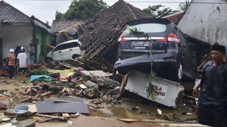 People inspect the damage at a tsunami-ravaged neighbourhood in Carita.