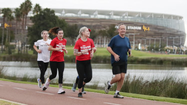 Opposition Leader Bill Shorten runs past the Optus Stadium during an early morning run along the Swan River in Perth.