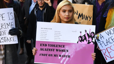 Protesters hold placards as they march through Melbourne to protest violence against women in June.