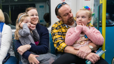 Tony Williams and wife Jacqui on board a metro train on Sunday with their daughters, Annika, left and Liesl.