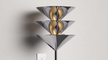 This wall light features a trio of cones nesting in a vertical stack supported by a metal framework.
