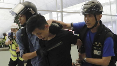 Policemen arrest a protester during Tuesday's violence at Hong Kong airport.