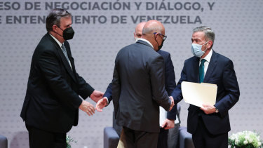 Jorge Rodriguez, president of the National Assembly of Venezuela and Gerardo Blyde Perez, head of the opposition delegation of Venezuela shake hands, right, at the start of talks in Mexico City.