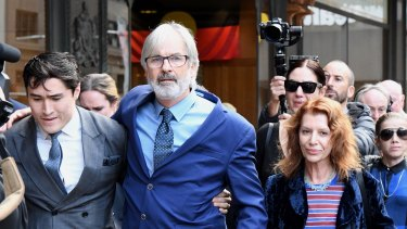 Actor John Jarratt (centre), wife Rosa Miano (right) and his lawyer Bryan Wrench (left) leave the Downing Centre Court on Friday.