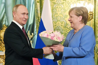 No dogs this time: Russian President Vladimir Putin, left, presents flowers to German Chancellor Angela Merkel during their meeting in the Kremlin on Friday.