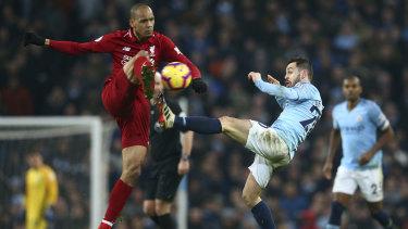 Liverpool's Roberto Firmino tangles with City's Bernardo Silva.