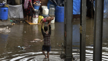 A man holds a child above his head as he wades through a waterlogged street in Mumbai.